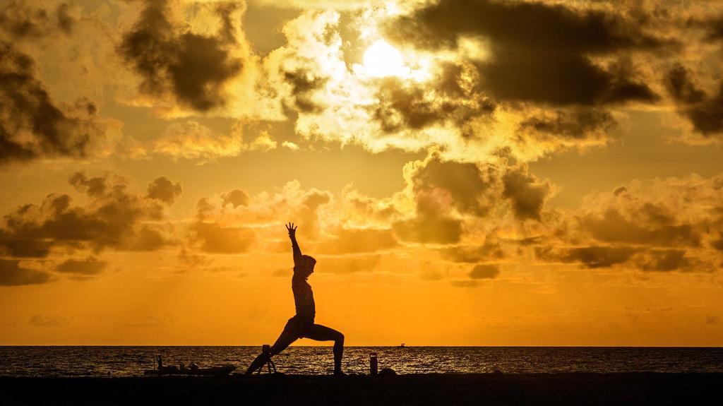 30.07.2020, USA, Palm Beach: Eine Frau macht am Midtown Beach bei Sonnenaufgang Yoga. Foto: Lannis Waters/Palm Beach Post via ZUMA Wire/dpa +++ dpa-Bildfunk +++