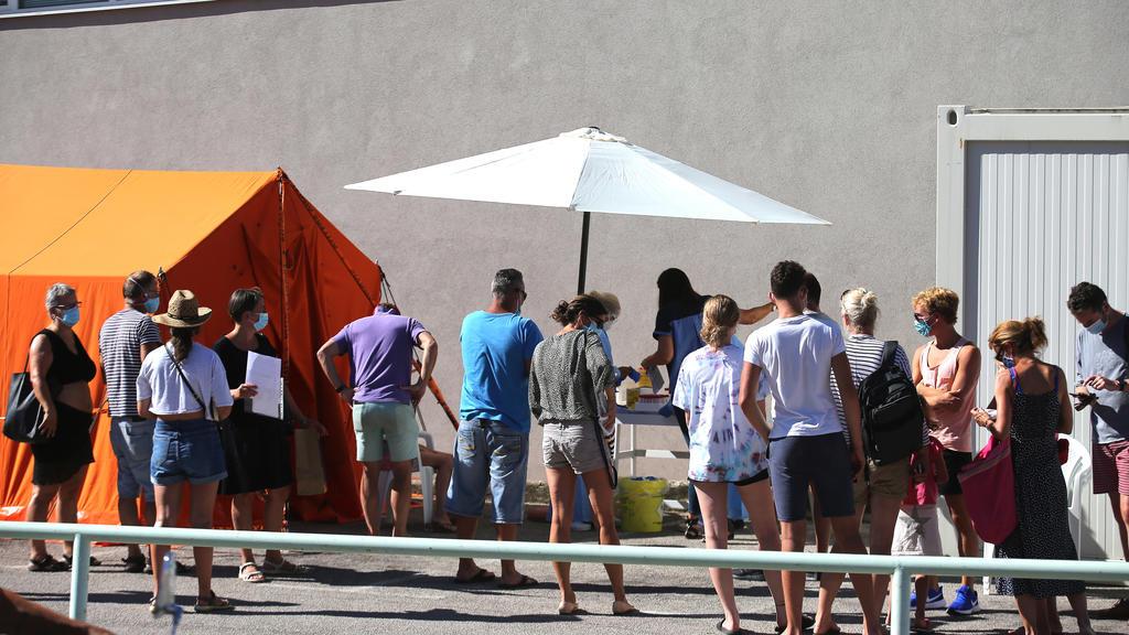Besucherinnen und Besucher warten vor einem Krankenhaus darauf, auf Covid-19-Symptome getestet zu werden.