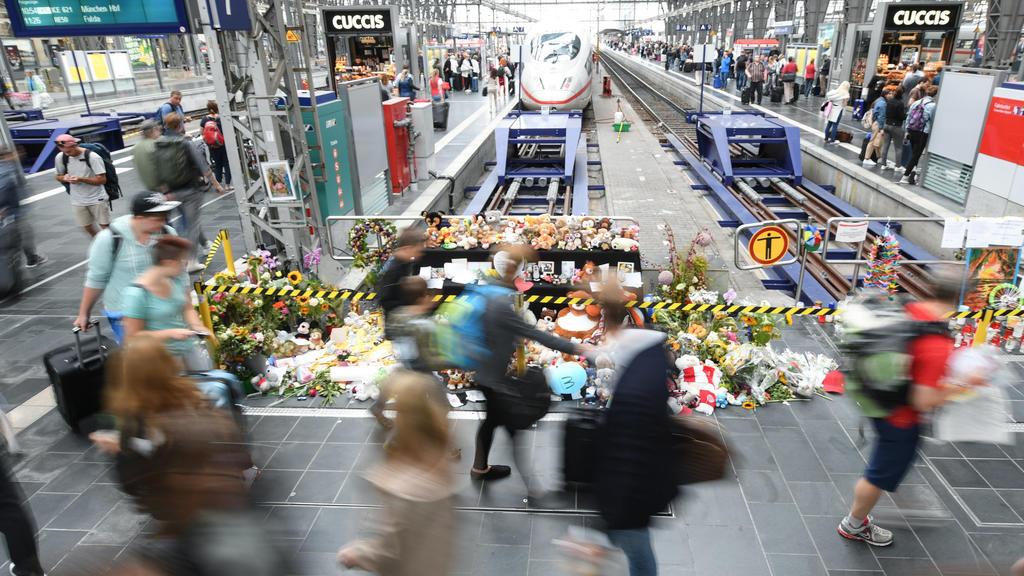 ARCHIV - 20.08.2019, Hessen, Frankfurt/Main: Passanten gehen am Gleis 7 des Hauptbahnhofs an einer Gedenkstelle vorbei, an der sich Blumen, Kuscheltiere und Beileidsbekundungen angesammelt haben (Aufnahme mit längerer Verschlusszeit). Am 29. Juli 201
