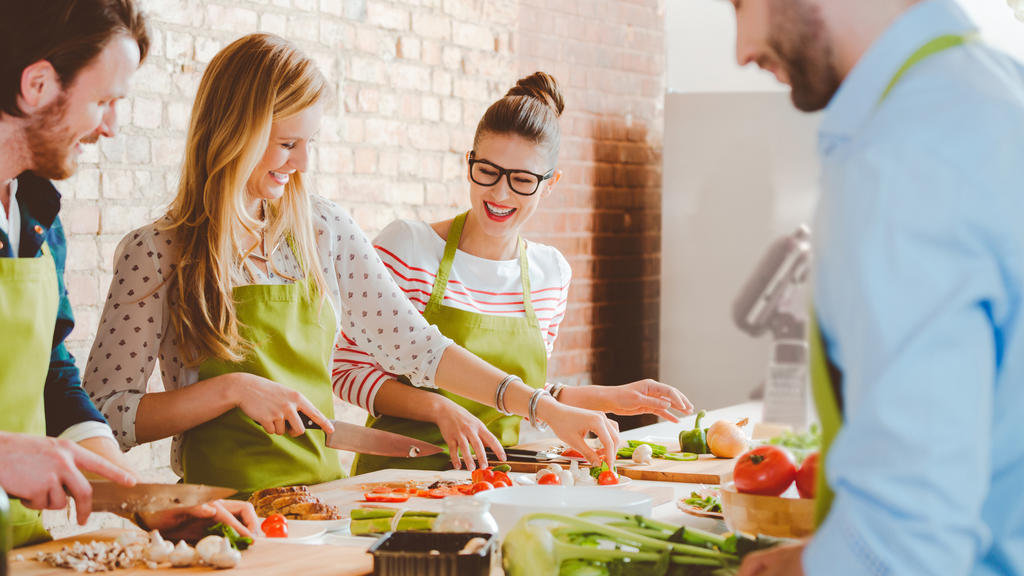 Group of people wearing aprons taking part in cooking class, preparing food, slicing vegetables, talking, laughing.