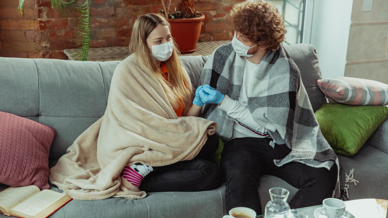 Paar in Schutzmasken und Handschuhen, zu Hause isoliert mit Coronavirus-Atemwegssymptomen wie Fieber, Kopfschmerzen, Husten.