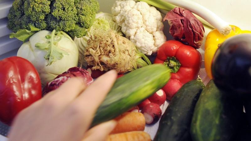 Eine Hand greift in einen Kühlschrank und man sieht ganz viel Gemüse, an dem sie sich bedient.