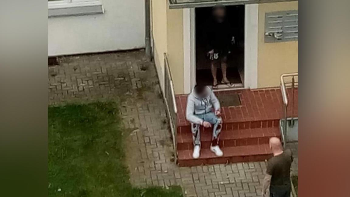 Hier sitzt der mutmaßliche Ex-Freund des Opfers mit blutiger Hose vor dem Hauseingang.