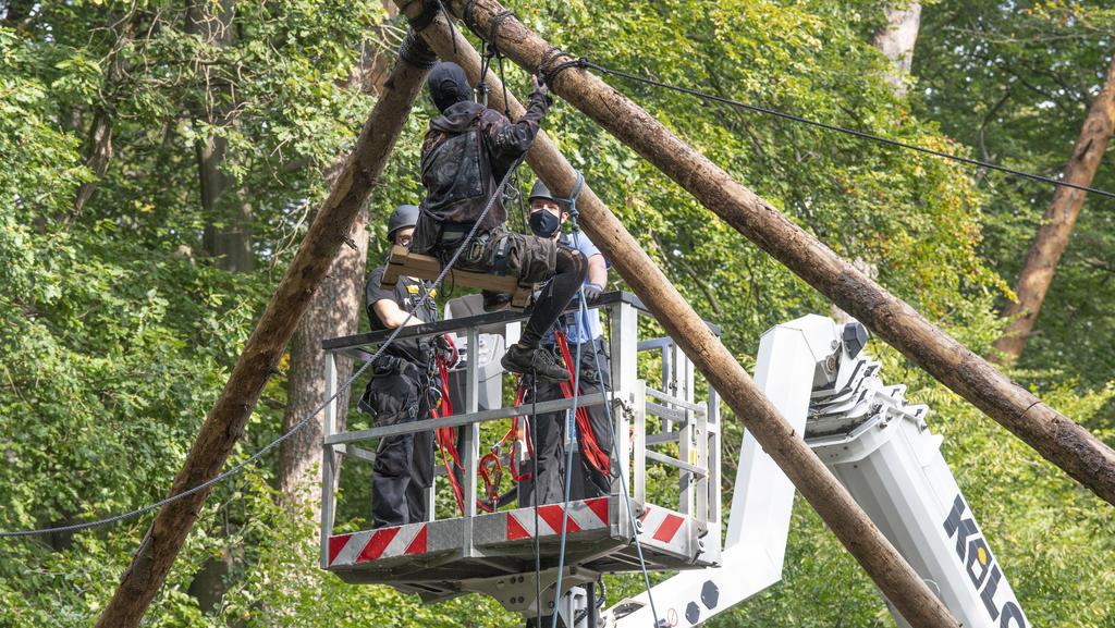 Die Polizei räumt Barrikaden von Waldbesetzern im Dannenröder Forst in Mittelhessen. Eine Aktivistin sitzt auf einer aus Stämmen errichteten Plattform,.
