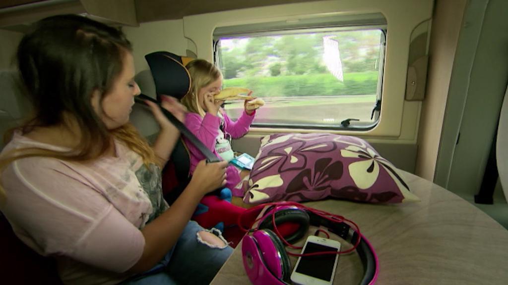 Kind und junge Frau sitzen angeschnallt auf Wohnmobil-Rückbank