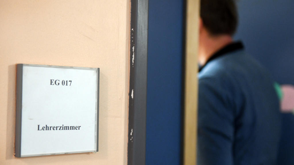 ARCHIV - 10.01.2018, Berlin: Ein Mann geht an einem Schild vorbei, das den Weg zum Lehrerzimmer weist. Gewalt gegen Lehrer hat laut einer Umfrage unter nordrhein-westfälischen Schulleitern in den vergangenen Jahren zugenommen. Wie die Lehrergewerksch
