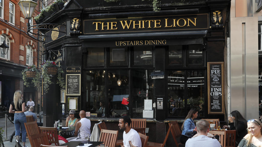 People sit outside the White Lion pub in London, Tuesday, Sept. 22, 2020. British Prime Minister Boris Johnson has slammed the brakes on the country's return to offices, saying people should work from home if possible to help slow the spread of the c