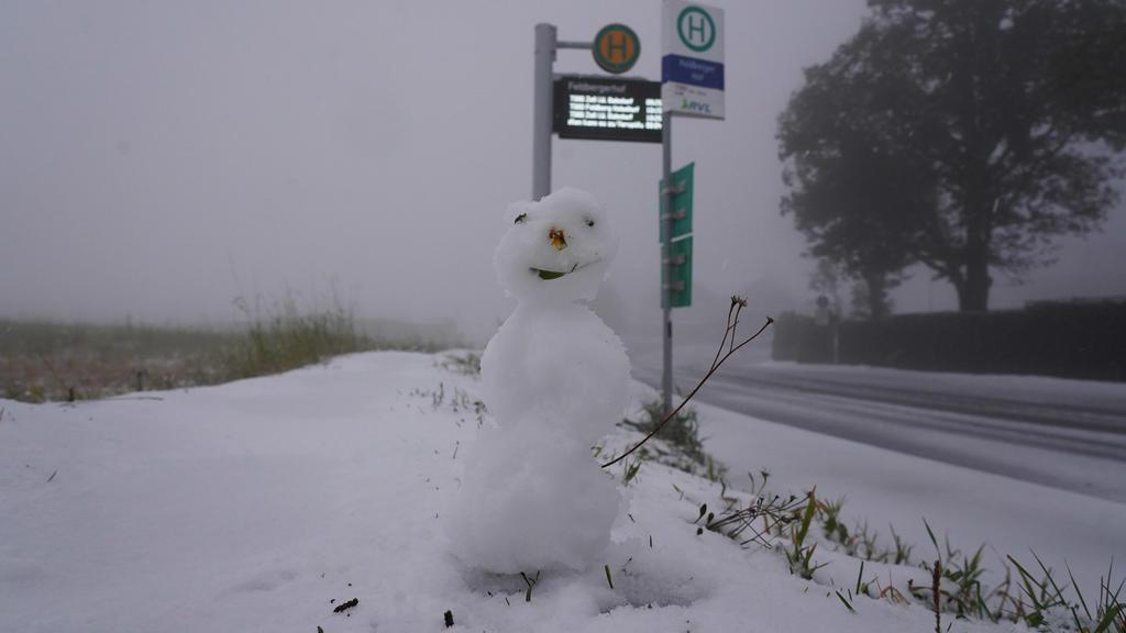 Ein kleiner Schneemann steht neben einer Bushaltestelle neben einer weiß verschneiten Straße auf dem Feldberg im Schwarzwald.