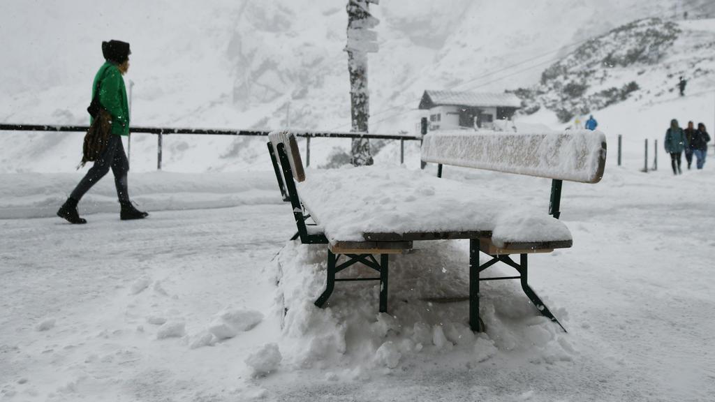 Eine Frau geht über die verschneite Terrasse der Bergstation am Osterfelderkopf im Wettersteingebirge nach einem Temperatursturz.