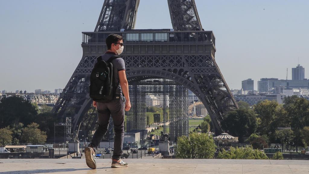 Frankreich, Paris: Ein Passant geht mit Mundschutzmaske über den Place du Trocadéro, während im Hintergrund ein Teil des Eiffelturms zu sehen ist