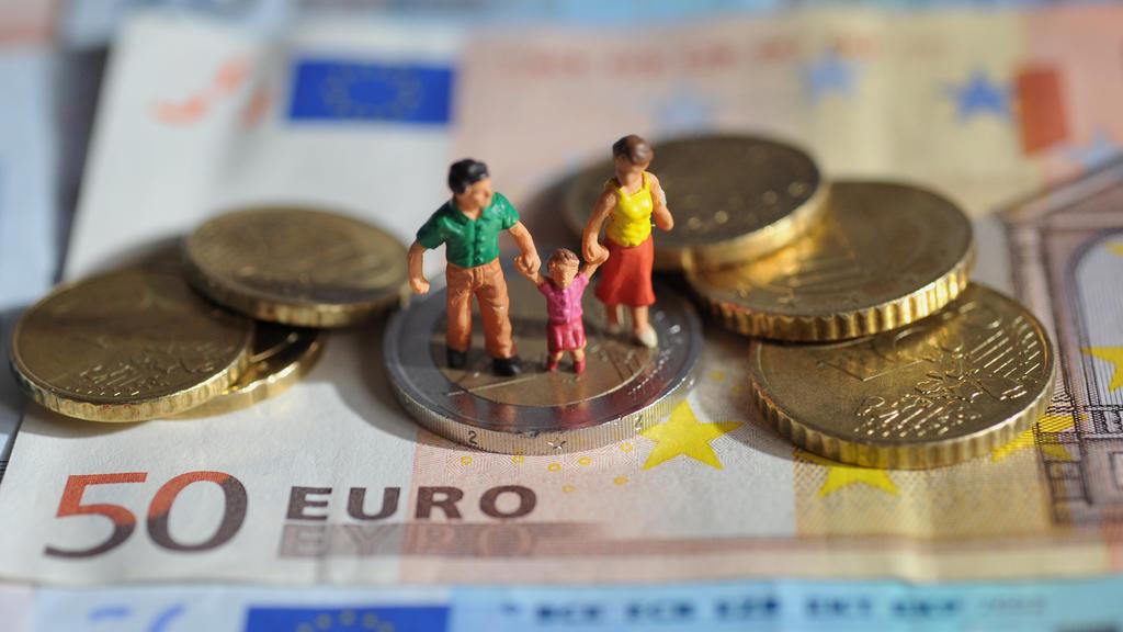 ILLUSTRATION - Ein Paar mit einem Kind steht auf einer Zwei-Euro-Münze, die auf einem 50-Euro-Schein liegt, aufgenommen am 16.02.2011. Foto: Andreas Gebert dpa/lby