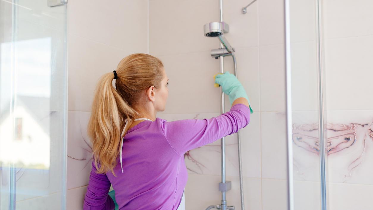 Frau reinigt die Dusche.