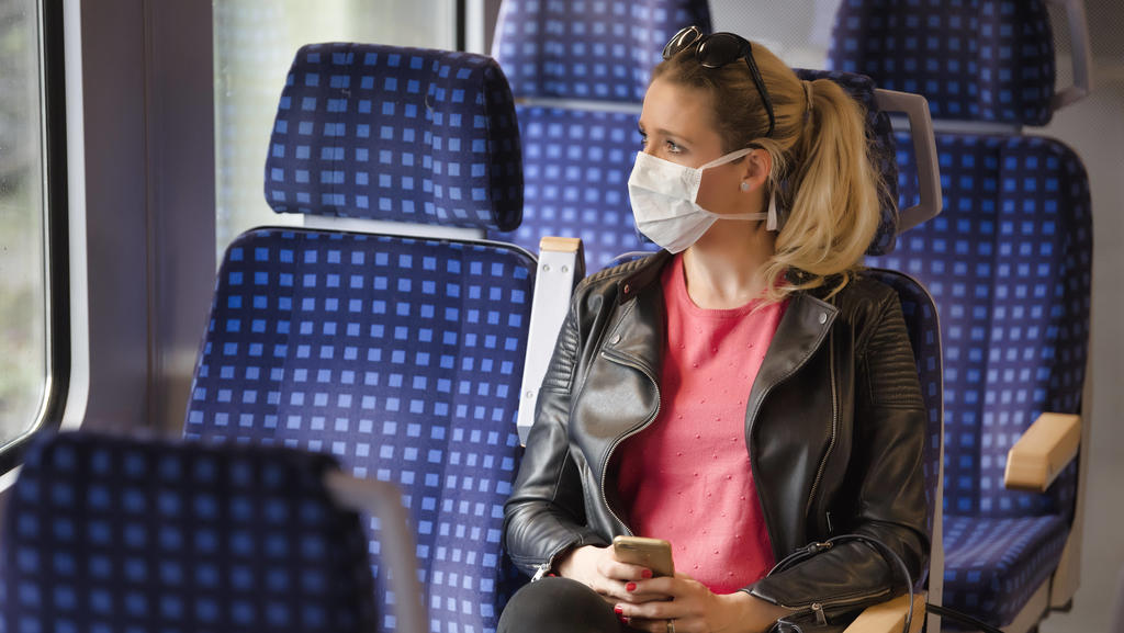 Frau mit Mundschutzmaske, sitzt in Zug, am Handy, Corona-Krise, Stuttgart, Baden-Württemberg, Deutschland Coronavirus *** Woman with a face mask, sitting in Zug, on a mobile phone, corona crisis, Stuttgart, Baden Württemberg, Germany Coronavirus
