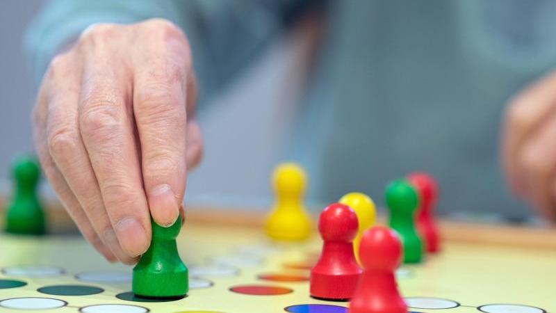 """Ein Mann zieht eine Figur des Spiels """"Mensch ärgere Dich nicht"""". Foto: Sebastian Gollnow/dpa/Archivbild"""