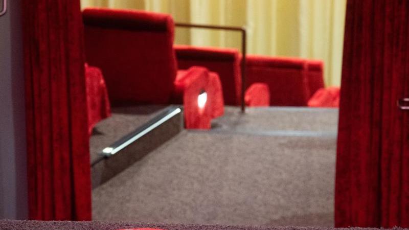 """Ein Schild mit Aufschrift """"Bitte Abstand halten"""" klebt vor einem Kinosaal. Foto: Julian Stratenschulte/dpa/Symbolbild"""