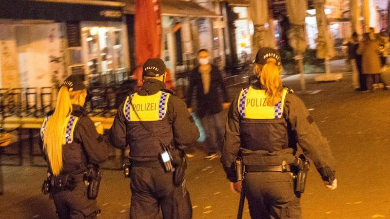 Polizisten gehen durch das Schanzenviertel. Foto: Daniel Bockwoldt/dpa