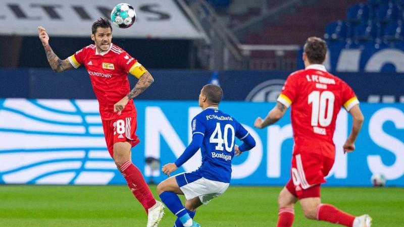 Schalkes Can Bozdogan (M) und Berlins Christopher Trimmel (l)kämpfen um den Ball. Foto: Guido Kirchner/dpa