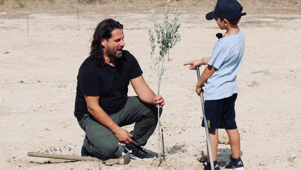 Adam Bousdoukos und kleiner Junge knien vor junger Pflanze