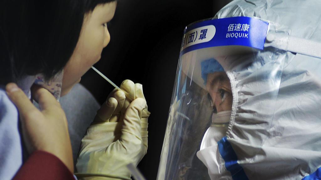 15.10.2020, China, Qingdao: Ein medizinisches Personal im Schutzanzug nimmt einen Abstrich von einem Kind in der Nähe eines Wohngebiets. Nach einem neuen Ausbruch des Coronavirus hat die ostchinesische Metropole Qingdao innerhalb von vier Tagen einen