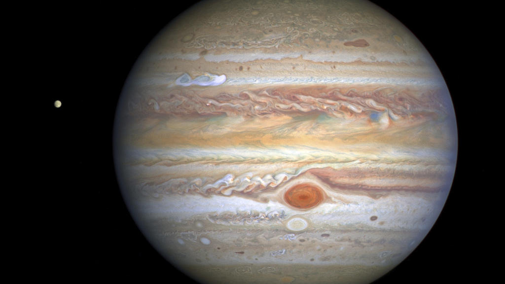 This Aug 25, 2020 image captured by NASA's Hubble Space Telescope shows the planet Jupiter and one of its moons, Europa, at left, when the planet was 406 million miles from Earth. The new photo was released by the Space Telescope Science Institute in