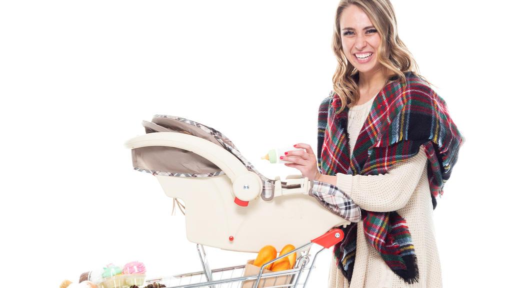 Mutter steht an einem Einkaufswagen mit Babyschale darauf