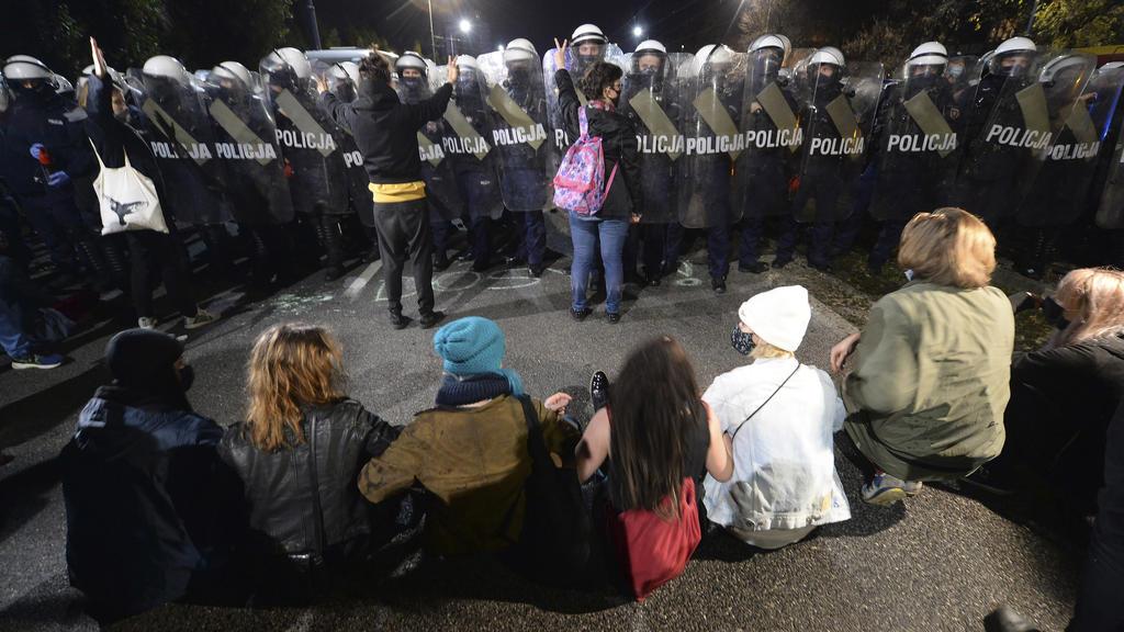 23.10.2020, Polen, Warschau: Polizisten bewachen das Haus des polnischen Vize-Ministerpräsidenten Kaczynski, währernd Demonstranten gegen die Entscheidung des Verfassungsgerichts protestieren. Das Verfassungsgericht in Warschau erklärte am Donnerstag