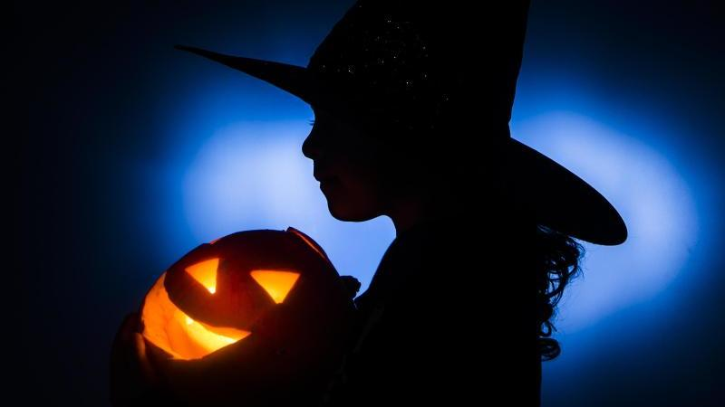 Ein junges Mädchen im Hexenkostüm hält einen beleuchteten Halloween-Kürbis im Arm. Foto: Danny Lawson/PA Wire/dpa/Symbolbild