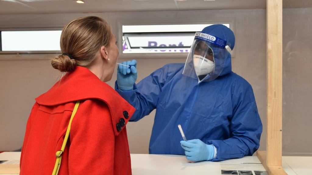 Ein Mitarbeiter der Stadt Köln nimmt im neuen Corona-Testzentrum am Hauptbahnhof bei einer Frau einen Abstrich.bei der der Eröffnung des neuen Corona Testzentrum am Kölner Hauptbahnhof. Hier können sich Reisende aus Risikogebieten innerhalb von 72 S