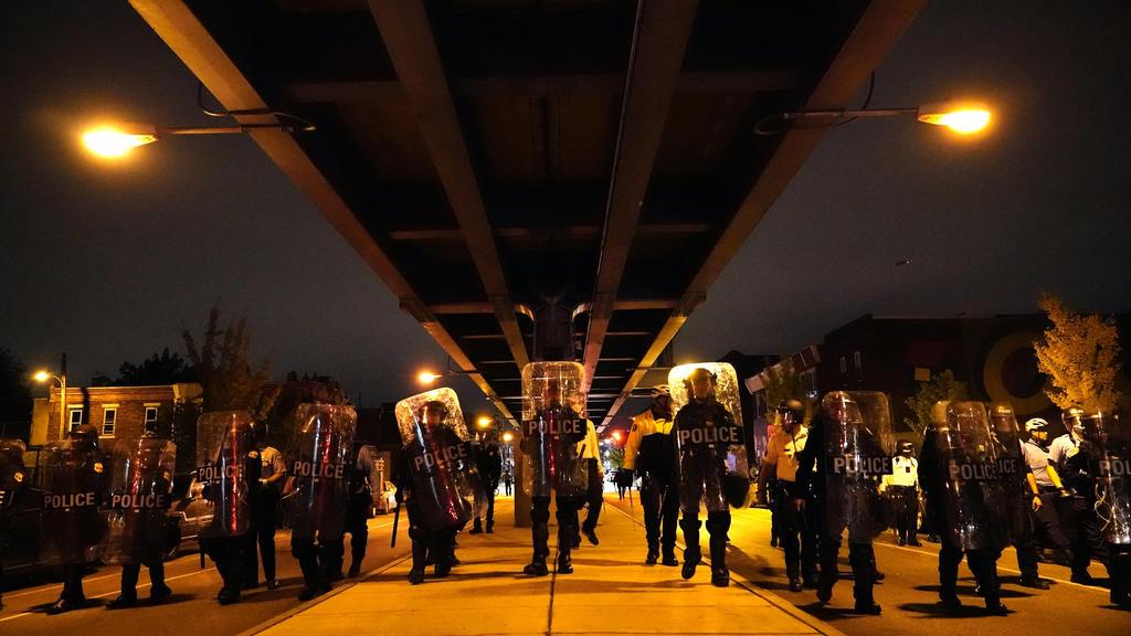 28.10.2020, USA, Philadelphia: Polizisten bilden während einer Demonstration gegen Polizeigewalt nach dem Tod eines Schwarzen durch Polizeischüsse eine Kette. Polizisten in der Stadt Philadelphia im US-Bundesstaat Pennsylvania hatten am 26. Oktober d