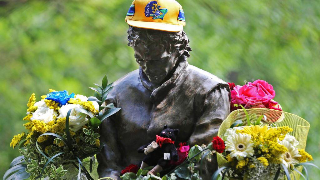ARCHIV - 01.05.2014, Italien, Bologna: In einem Park nahe der Formel-1-Rennstrecke in Imola erinnert eine mit Blumen geschmückte Statue an den tödlich verunglückten Rennfahrer Ayrton Senna. Der Brasilianer war 1994 in Imola bei einem Unfall gestorben