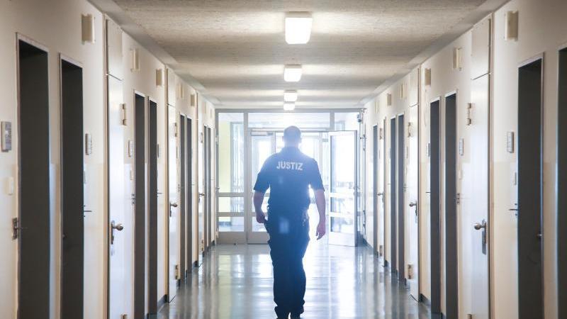 Ein Vollzugsbeamter geht in der JVA Billwerder in Hamburg einen Gang entlang. Foto: picture alliance/Ulrich Perrey/dpa/Archivbild