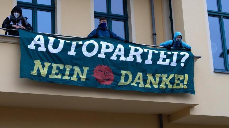 Demonstranten stehen auf dem Balkon der Grünen-Geschäftsstelle. Foto: Paul Zinken/dpa-Zentralbild/dpa/Archivbild