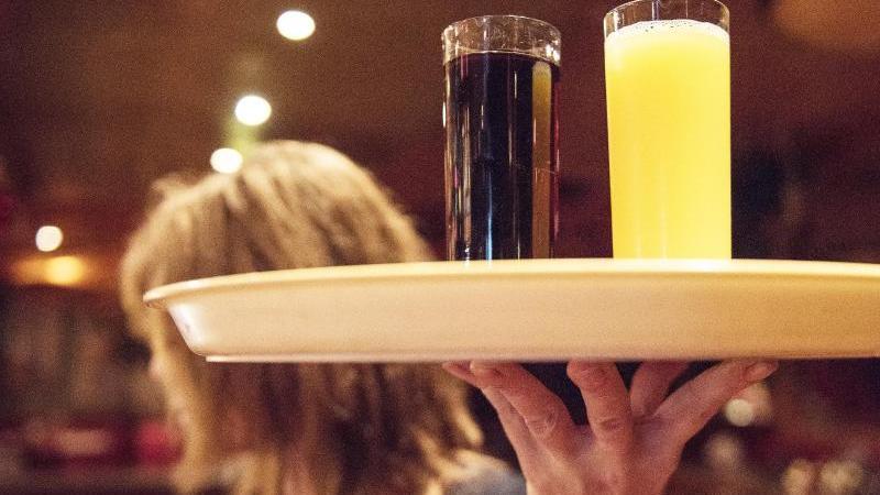 Eine Kellnerin trägt ein Tablett mit Getränken. Foto: Caroline Seidel/dpa/Archiv/Symbolbild