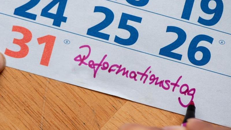 """Eine Frau schreibt """"Reformationstag"""" neben die Zahl 31 in einen Kalender. Foto: Swen Pförtner/dpa/Archivbild/Illustration"""