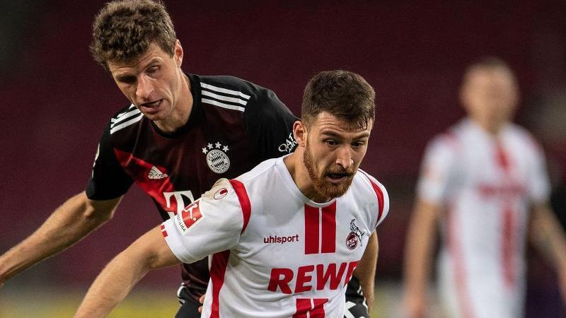 Kölns Salih Özcan (r) und Bayerns Thomas Müller kämpfen um den Ball. Foto: Marius Becker/dpa-Pool/dpa/Archivbild