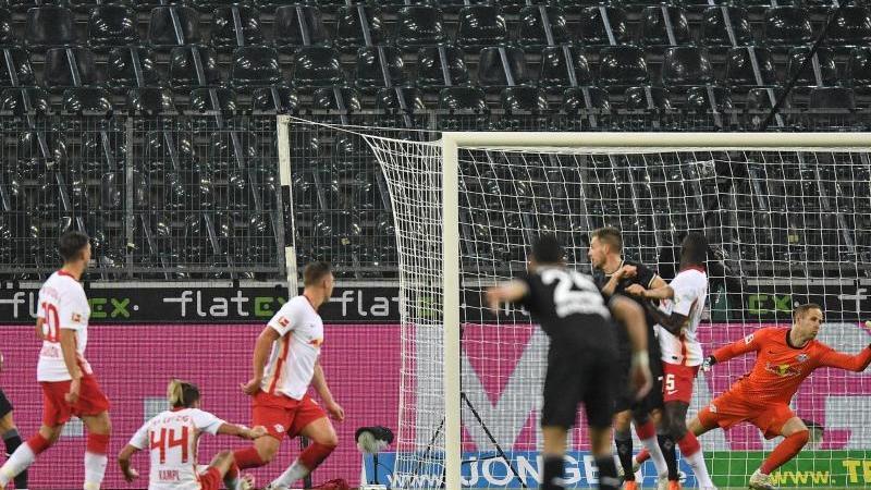 Mönchengladbachs Hannes Wolf (l) erzielt das 1:0 gegen Leipzigs Torwart Peter Gulacsi. Foto: Martin Meissner/Pool AP/dpa