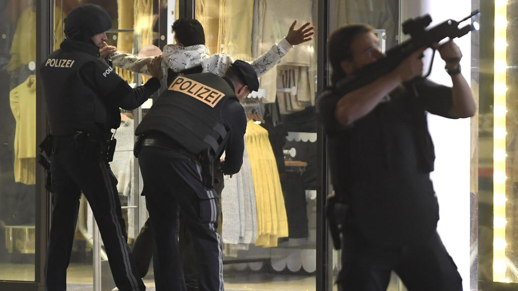 02.11.2020, Österreich, Wien: Schwerbewaffnete Polizisten kontrollieren in der Wiener Innenstadt eine Person. Ein Beamter hat seinGewehr im Anschlag. Bei den Schüssen in Wien handelt es sich nach den Worten von Österreichs Innenminister augenscheinl