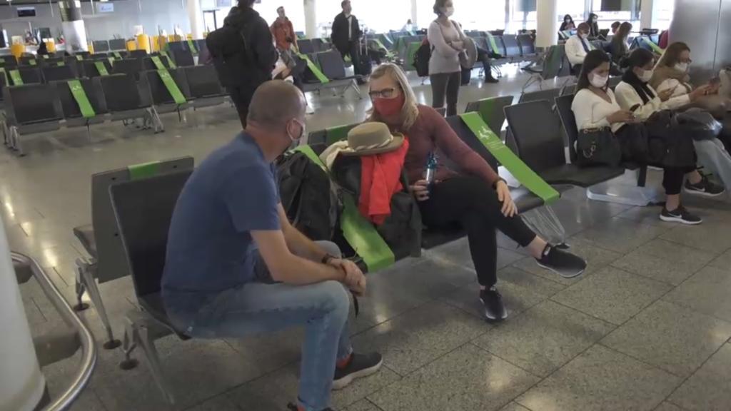 Mann und Frau an Gate auf Sitzplätzen