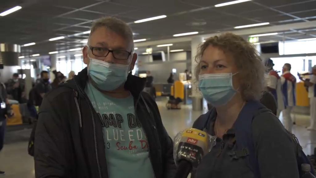Mann und Frau mit Maske am Gate