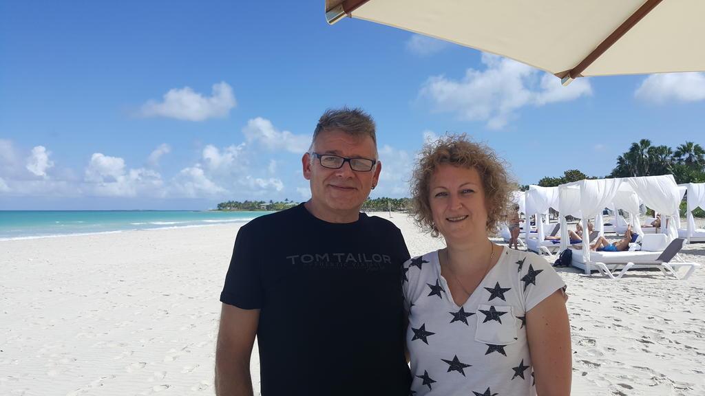 Mann und Frau stehen am Strand unter Sonnenschirm