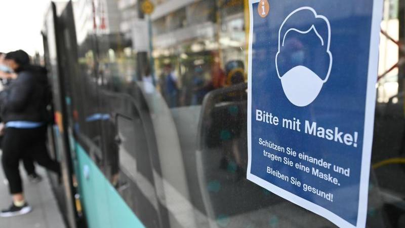 """Ein Plakat mit der Aufschrift """"Bitte mit Maske! Schützen Sie einander und tragen Sie eine Maske. Bleiben Sie gesund!"""" hängt an einem Bus. Foto: Arne Dedert/dpa/Archivbild"""