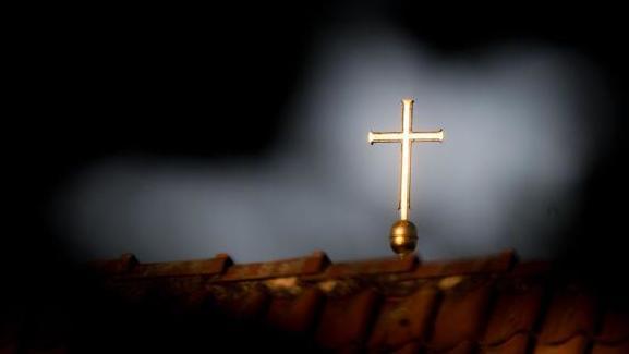 Ein goldenes Kreuz auf einer evangelischen Kirche.