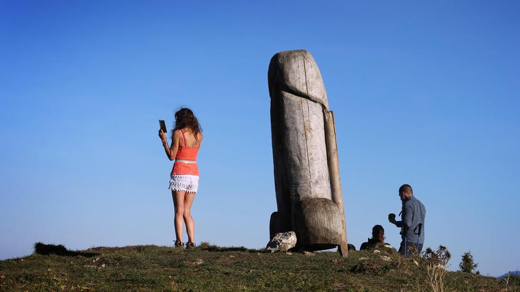 14.11.2020, Bayern, Rettenberg: Eine Frau macht ein Selfie mit der zwei Meter hohen Penis-Skulptur aus Holz auf dem Grat des Grünten. Seit vier Jahren steht das ungewöhnliche «Kulturdenkmal» auf dem Berg. (zu dpa «Kulturdenkmal»: Holzpenis auf Allgäu