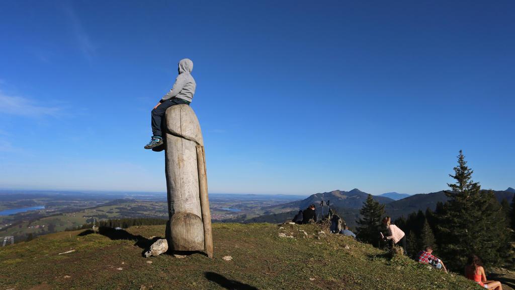 14.11.2020, Bayern, Rettenberg: Ein Junge sitzt auf der zwei Meter hohen Penis-Skulptur aus Holz auf dem Grat des Grünten. Seit vier Jahren steht das ungewöhnliche «Kulturdenkmal» auf dem Berg. (zu dpa «Kulturdenkmal»: Holzpenis auf Allgäuer Berg ste