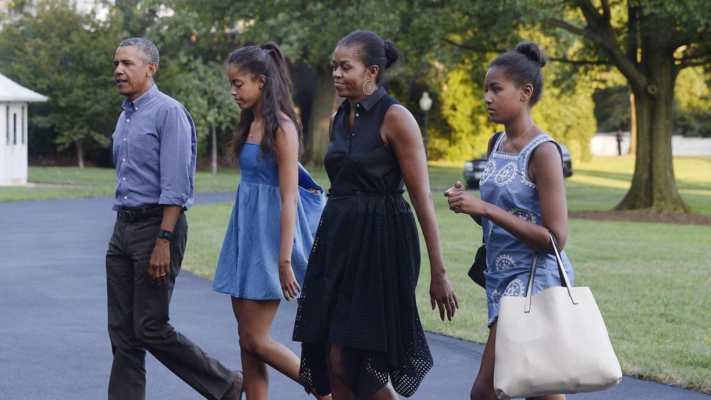 ARCHIV - 23.08.2015, USA, Washington: Barack Obama (l), ehemaliger US-Präsident, Ehefrau Michelle (2.v.r) und die Töchter, Sasha (2.v.l), und Malia (r), treffen im Weißen Haus ein, nachdem sie von ihrem Urlaub in Martha's Vineyard zurückgekehrt sind.