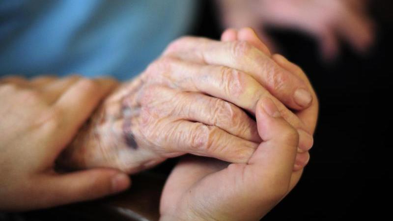 Eine Pflegekraft hält in einem Seniorenheim die Hand einer Bewohnerin. Foto: Daniel Reinhardt/dpa/Archivbild