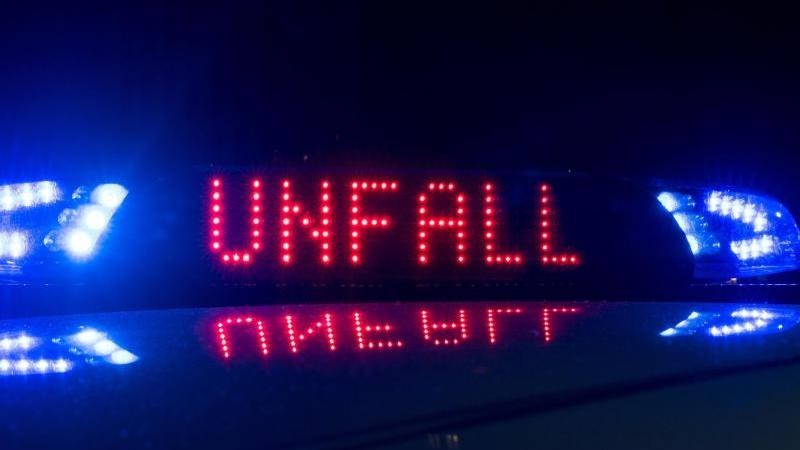 """Das Blaulicht auf einem Fahrzeug der Polizei leuchtet in der Dunkelheit, während auf dem Display """"Unfall"""" zu lesen ist. Foto: Monika Skolimowska/dpa-Zentralbild/ZB/Symbolbild"""