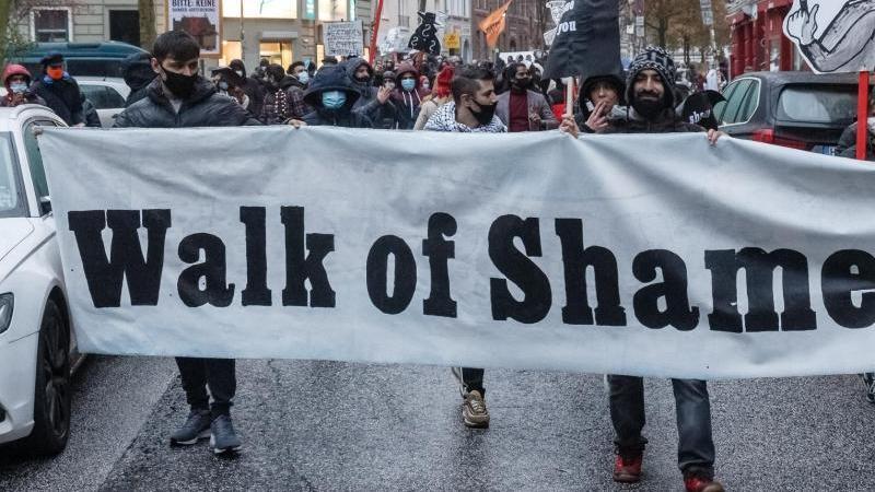 """Teilnehmer der Demonstration halten ein Transparent mit der Aufschrift """"Walk of Shame"""". Foto: Markus Scholz/dpa"""