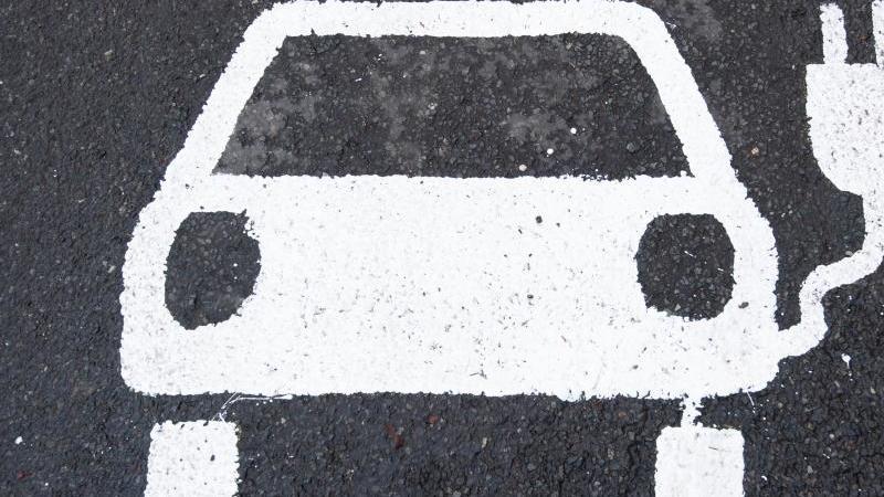 Ein Symbol für ein E-Auto markiert einen Parkplatz neben einer E-Ladesäule. Foto: Julian Stratenschulte/dpa/Symbolbild