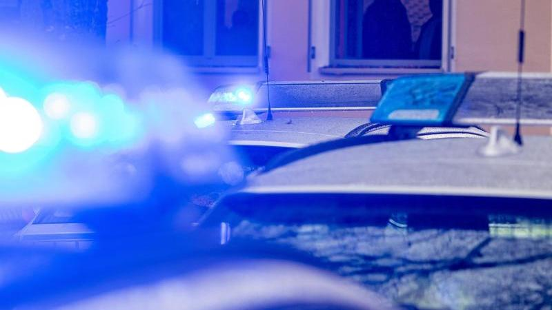 Polizeifahrzeuge stehen mit Blaulicht vor einem Haus. Foto: Armin Weigel/dpa/Symbolbild